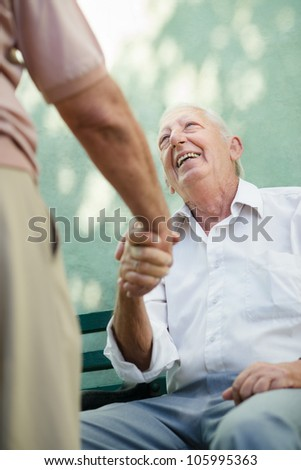 Active retirement, two old male friends talking and shaking hands on bench in public park - stock photo