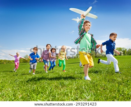 Active running kids with boy holding airplane toy - stock photo