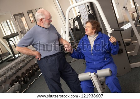 Active Senior Adult Couple Working Out Together in the Gym. - stock photo
