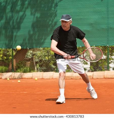 Active senior man, playing tennis - stock photo