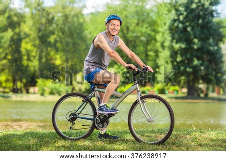 Active senior man riding a bike in park on a beautiful summer day shot with tilt and shift lens - stock photo