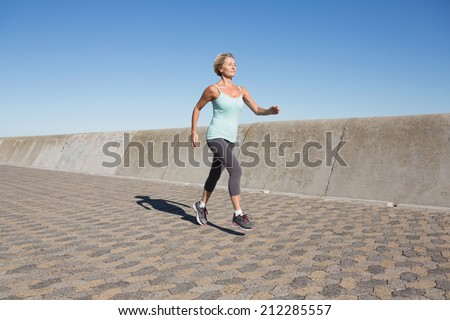 Active senior woman jogging on the pier on a sunny day - stock photo