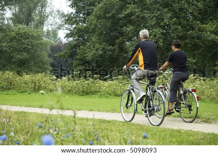 Active seniors biking in the park, from behind. - stock photo