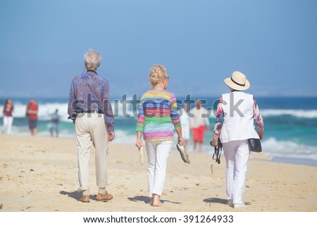 Active seniors enjoying beach walk. Active ageing, healthy lifestyle and well-being throughout life course concept. - stock photo