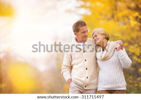 Active seniors on a walk in autumn forest - stock photo