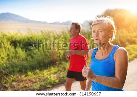Active seniors running outside in green nature - stock photo