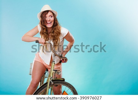 Active smiling woman riding bike bicycle. Young girl in hat, white shirt and shorts. Healthy lifestyle and recreation leisure activity. Studio shot. - stock photo