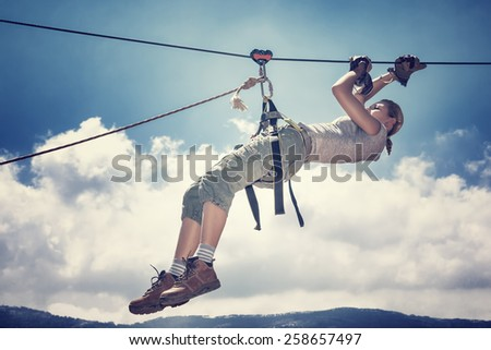 Active sportive woman hanging on the tightrope between mountains, playing rappel sport, extreme lifestyle, great sportive achievement - stock photo