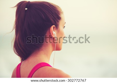 Active Sports Lifestyle with Modern Technology. Young fitness woman listening to music working out. - stock photo