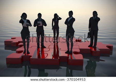 Active team on Jigsaw puzzle by the sea at sunrise.  A successful active team working like pieces of a jigsaw puzzle since sunrise thanks to their leader. - stock photo