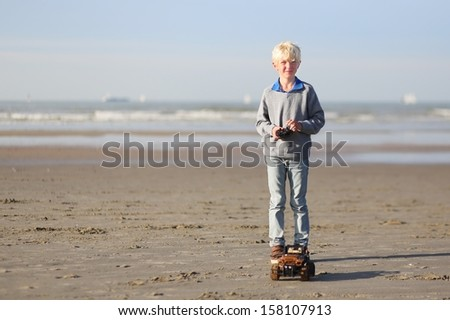 Active teenager boy plays with remote control car on the beach - stock photo