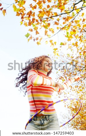 Active teenager girl playing hoola hoop in a park with orange and brown leaves on the trees, having fun and playing during a sunny autumn day. - stock photo