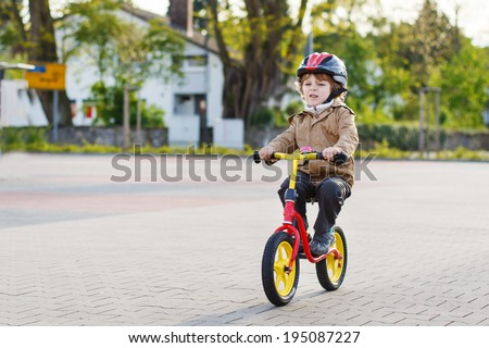 Active toddler boy having fun and riding his bike  in the city - stock photo
