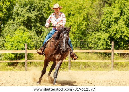 Active western cowgirl woman in hat training riding horse. American girl in countryside ranch. Horseback sport activity. - stock photo