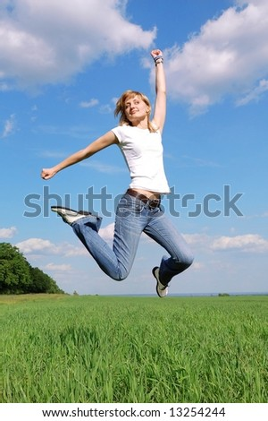 Active woman jumping hight up at the blue sky background - stock photo