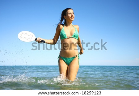 Active woman playing ball in the ocean - stock photo