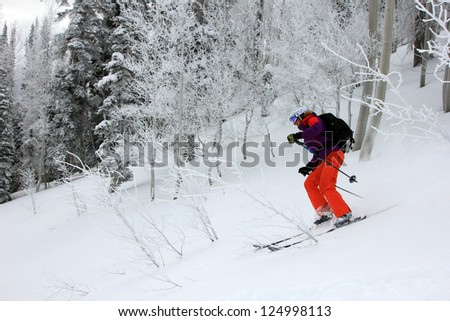 Active woman smiling as she ski's through a frosted forest, Utah, USA. - stock photo