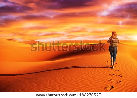 Active woman trekking along desert, walking alone in the dune, discovering nature, expedition to the wilderness, travel and tourism concept - stock photo