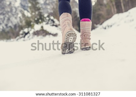 Active woman walking away from the camera through winter snow wearing pale pink boots in the countryside, with copyspace in the foreground. Retro filter effect. - stock photo