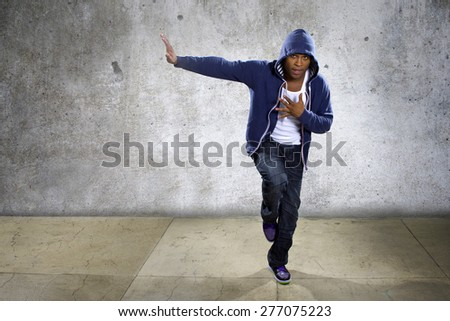 Active young black male dancing hip hop style in an urban setting.  He is wearing a blue hoodie and is on a concrete background with copyspace. - stock photo
