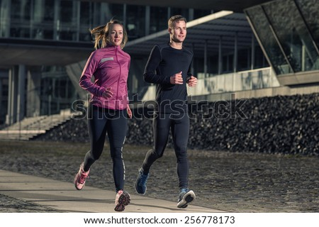 Active young couple jogging side by side in an urban street during their daily workout in a health and fitness concept - stock photo