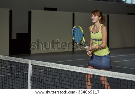 Active young female in sportswear playing tennis on the court. Pretty girl with racket practicing tennis with her coach. - stock photo