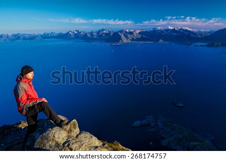 Active young man standing on the top of mountain Festvagtinden with breathtaking scenery of Lofoten islands, Norway - stock photo