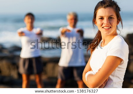 active young teenage girl posing with her parents exercise at the background - stock photo
