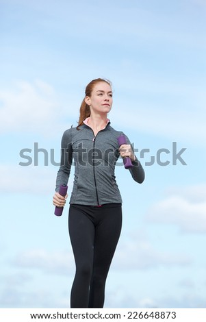 Active young woman keeping fit by power walking outdoors - stock photo