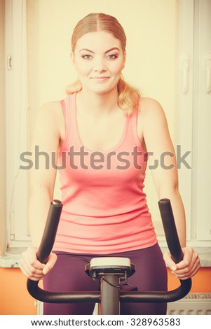 Active young woman working out on exercise bike stationary bicycle. Sporty girl training at home. Fitness and weight loss concept. - stock photo