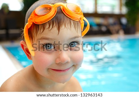 Activities on the pool. Cute boy swimming and playing in water in swimming pool - stock photo
