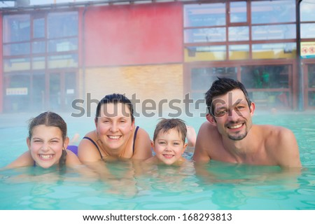 Activities on the pool. Portrait of happy family of four relaxing in termal swimming pool - stock photo