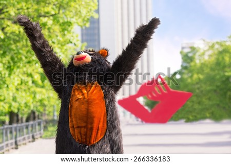 actor dressed as bear enjoys the sun on avenue of park on background of red stars - stock photo