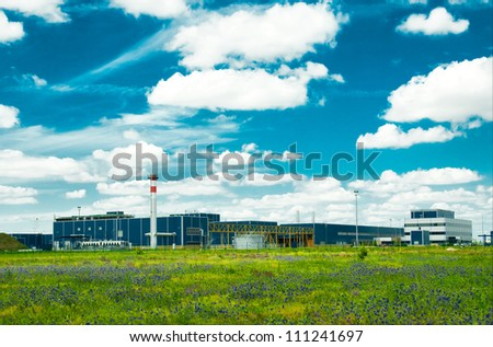 actory in the middle of a green meadow on a cloudy day - stock photo