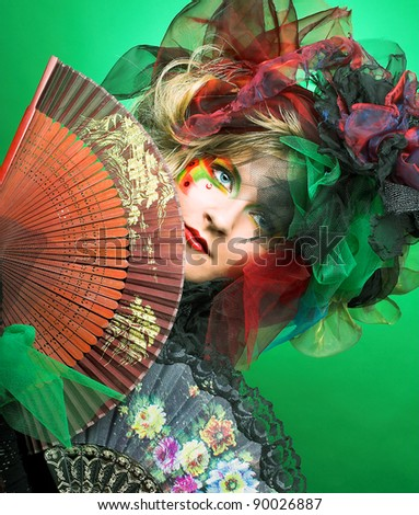 Actress. Young woman in creative image with two fans. - stock photo