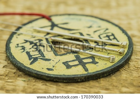 Acupuncture needles with antique chinese coin - stock photo