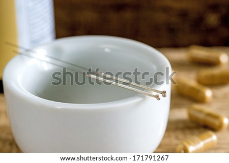 acupuncture needles with mortar and chinese herbal pills - stock photo
