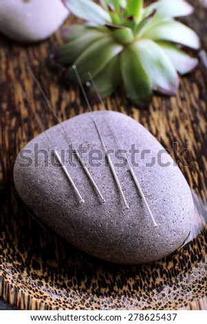 Acupuncture needles with spa stone on tray, closeup - stock photo