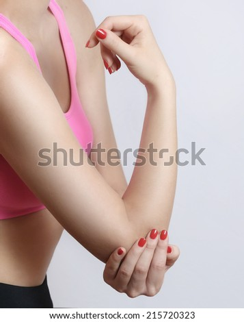 Acute elbow pain, Woman holds hand on his pain elbow. - stock photo