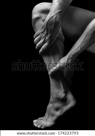 Acute pain in the male calf muscle, black and white image - stock photo