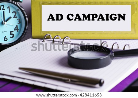 Ad Campaign - Yellow Office Folder on Background of Working Table with Magnifying glass, a pen and clock -business and finance concept - stock photo