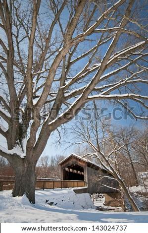 Ada Covered Bridge Wintertime at the historic Ada Covered Bridge in Kent County, Michigan. - stock photo