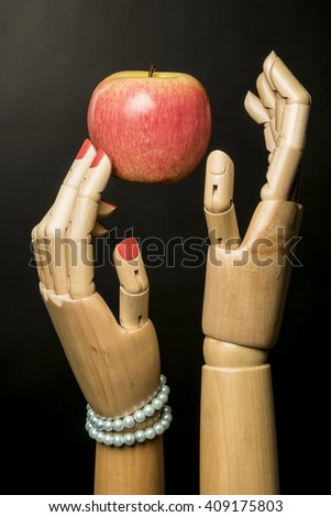 Adam, Eve and the apple. Black background. Two fingers with painted nails woman touching the fruit. - stock photo
