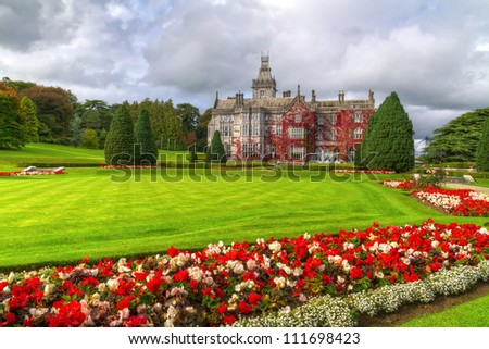 Adare gardens and castle in red ivy in Ireland - stock photo