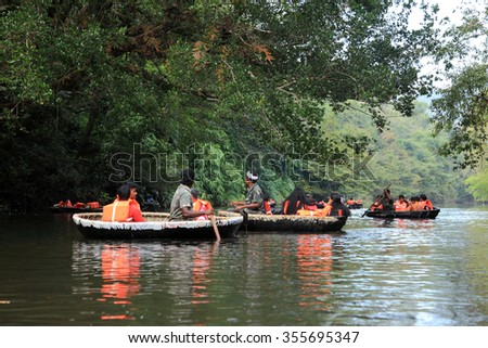 ADAVI, INDIA - DEC 27:Tourists go around in a bowl boat through the river Kallar on December 27,2015 in Adavi, Kerala, India. Eco tourism is promoted by the Government in the forest regions of Adavi. - stock photo