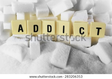 addict block letters word on pile of sugar cubes close up in sugar addiction , sweet nutrition , unhealthy eating and diet concept - stock photo