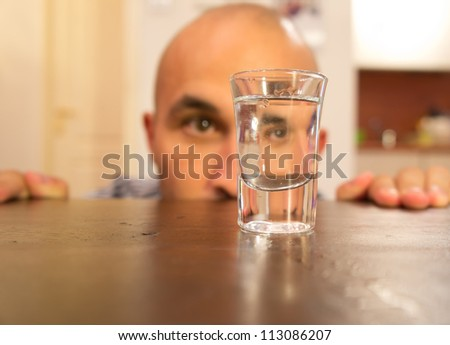 Addicted man looking at a glass filled with alcohol - stock photo