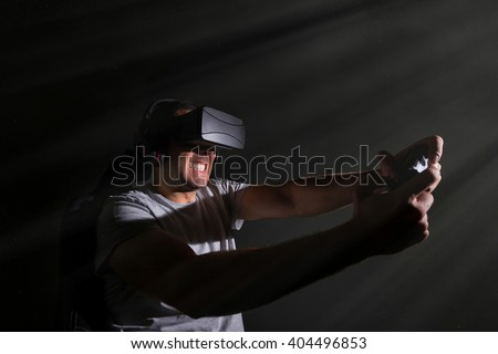 addicted young man playing a virtual reality video game; video game addiction futuristic concept - stock photo