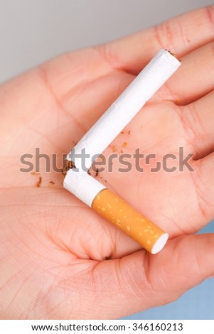 Addiction. Closeup of the broken cigarette on female hand. Quit smoking. Studio shot. - stock photo