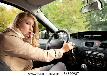 addiction smokingteen  woman  driving a car and drinking beer - stock photo